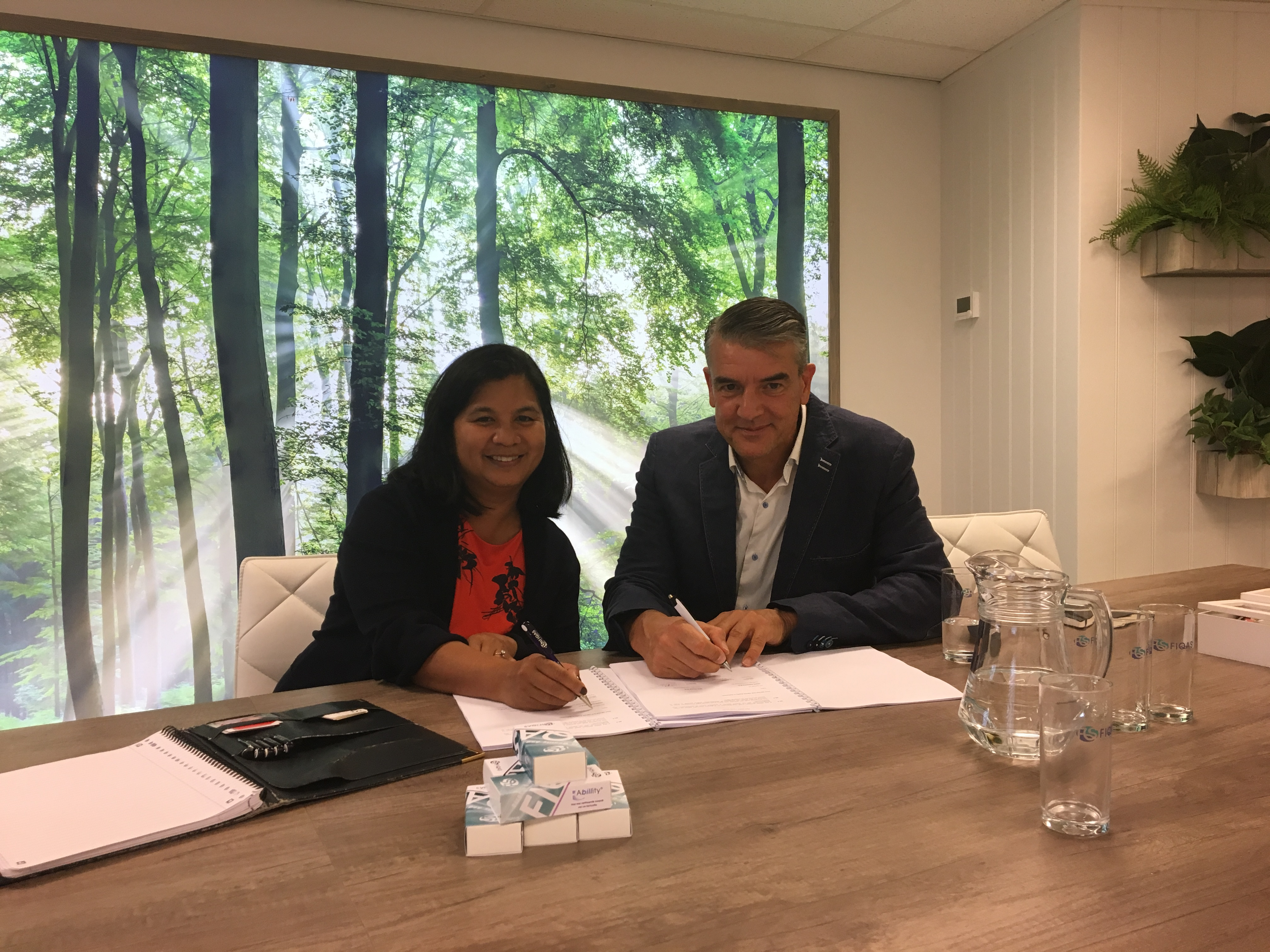 Lydia Ventura (CFO OLX) and Rob Geleijn (CEO FIQAS) undersign the agreement at FIQAS HQ